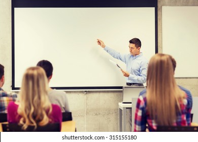 education, high school, technology and people concept - teacher with notepad, laptop computer standing in front of students and showing something on white board in classroom
