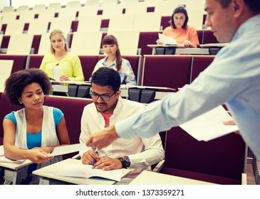 education, high school, university, learning and people concept - teacher giving tests to students at lecture