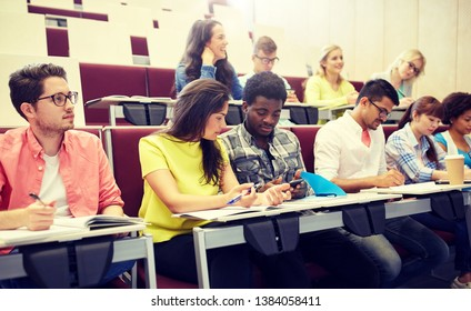 education, high school, university, learning and people concept - group of international students with smartphone at lecture