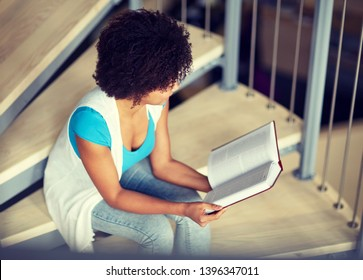 education, high school, university, learning and people concept - smiling african american student girl reading book sitting on stairs at library
