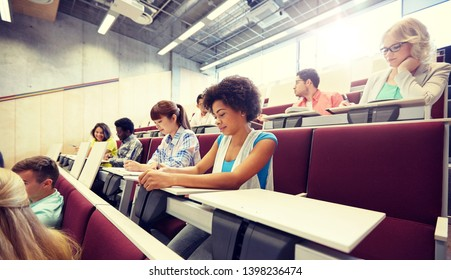 education, high school, university, learning and people concept - group of international students with notebooks writing at lecture hall