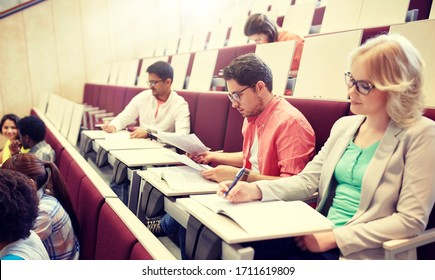 education, high school, university, learning and people concept - group of international students writing test at lecture hall