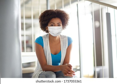 education, high school, university, learning and people concept - african american student girl wearing face protective medical mask for protection from virus disease sitting on stairs at library