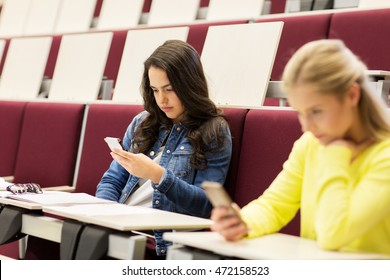education, high school, university, learning and people concept - student girls with smartphones on lecture