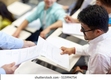 education, high school, university, learning and people concept - teacher giving exam test to indian student man at lecture