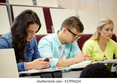 education, high school, university, technology and people concept - group of students with smartphone and book at lecture