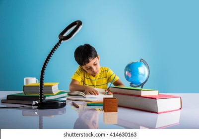 Education at home concept - Cute little Indian/Asian boy studying or completing home work on study table with pile of books, educational globe, laptop computer, coffee mug etc