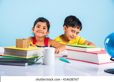 Education at home concept - Cute little Indian/Asian kids studying or completing home work on study table with pile of books, educational globe, laptop computer, coffee mug etc
