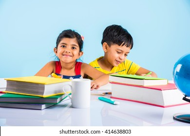 Education at home concept - Cute little Indian/Asian kids studying on study table with pile of books, educational globe, laptop computer, coffee mug etc