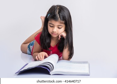 Education at home concept - Cute little Indian/Asian girl studying with pile of books and coffee mug while sitting on the floor at home. Isolated over white background