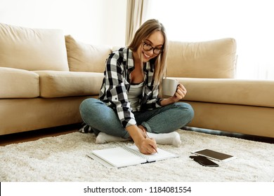 Education. Home. Girl in casual clothes and eyeglasses is making notes, holding a cup and smiling while studying on the floor at home