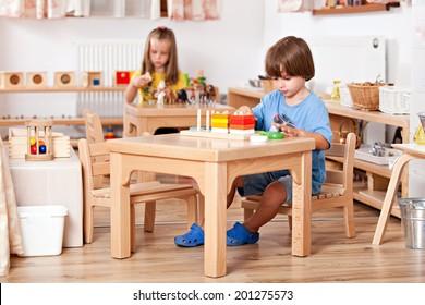 Bildungs-Bild aus einem Kindergarten: Kind, das mit Spielzeug am Tisch spielt