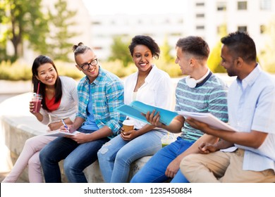 education, international and people concept - group of happy exchange students with notebook and takeaway drinks talking outdoors