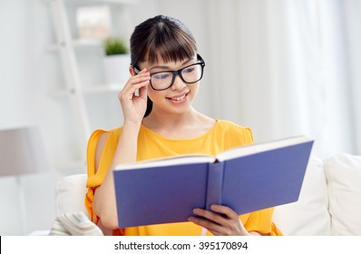 education, knowledge, vision, literature and people concept - smiling young asian woman or student girl in glasses reading book at home