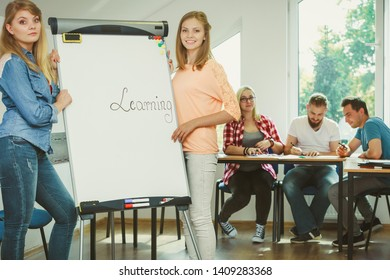 Education, knowledge, wisdom and learn new things concept - student girl writing Learning word on whiteboard in front of students her group mates in classroom