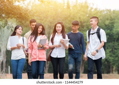 Education learning Concept: Confident Asian Students groups walking hold books, tablet notebook at Outside classroom in university with smilie and happy.