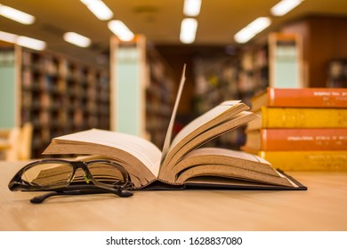 Education learning concept with old book, pile of literature texts and eyeglasses in library with the blur background of aisles of bookshelves. For traditional academic learning concept. Copy space.