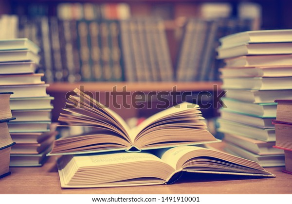 Education learning concept with opening book or textbook in old library, stack piles of literature text academic archive on reading desk and aisle of bookshelves in school study class room background