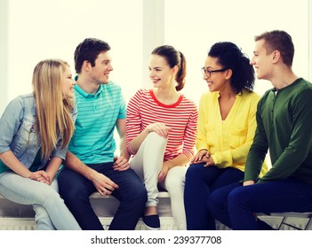 education, leisure and happiness concept - five smiling teenagers having fun at home or school