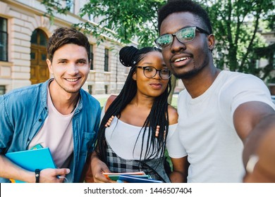 Education, lifestyle, leisure and technology concept.Handsome african man student in eyewear with two multiethnic friends making selfie together in park during relax free time.