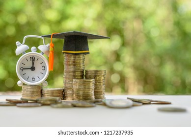 Education loan for study overseas / student loan fund concept : Mortarboard, white clock on coins, depicts loans issued for the purpose of attending an academic university and pursuing academic degree