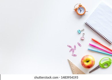 Education mockup with pupil's stationery, clock, apple and textbook on white background top view