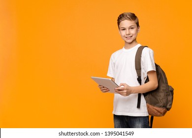 Education and modern technologies. Schoolboy with backpack using tablet computer and smiling on orange background, empty space