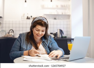 Education, modern technology, occupation and communication concept. Chubby happy female student smiling joyfully while doing homework, recollecting something funny, sitting in front of open laptop