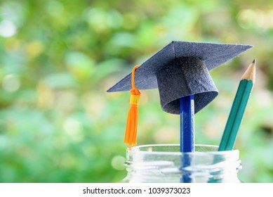 Education is the most powerful weapon or knowledge is power concept : Black graduation cap or hat with orange tassel on a pencil in a clear glass bottle, a green pencil with sharp tip points upward.