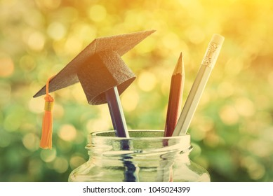 Education is the most powerful weapon or knowledge is power concept : Black graduation cap or hat with a tassel on a pencil in a clear glass jar / bottle, silver pencil with white rubber points upward