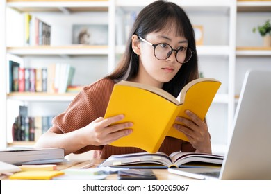 Education online learning or self study concept. Collage girl do reseaching and finding from books and internet online.
