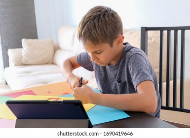Education, paper crafts for kids. Child cutting colored paper with scissors. Boy looking video tutorial and making paper craft project at home