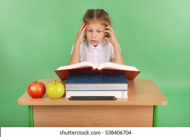 Education, people, children and school concept - young school girl sitting at table with book over green