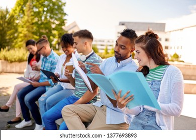 education and people concept - group of happy students with notebooks, tablet computer and takeaway drinks learning outdoors