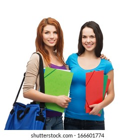 education and people concept - two smiling students with bag and folders standing