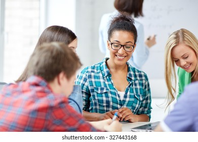 education, people, friendship, technology and learning concept - group of happy international high school students or classmates with workbook learning in classroom