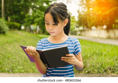 Education, people and learning concept - girl reading book outdoors