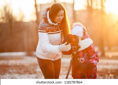 Education photography using tripod and SLR camera. Mom the photographer with child in sunset park