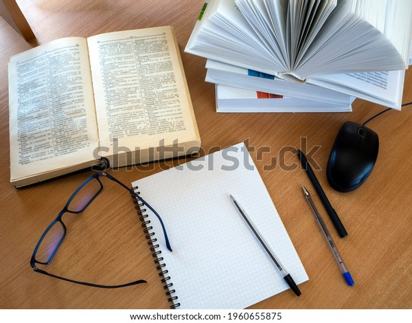 Education process. Reading monographs, scientific literature, note-taking, educational process, online learning. Background with books and other items.
