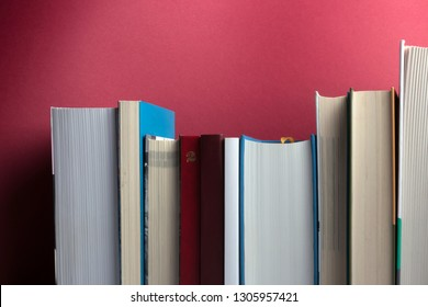 Education and reading concept. Bookshelf with row of important books on red background