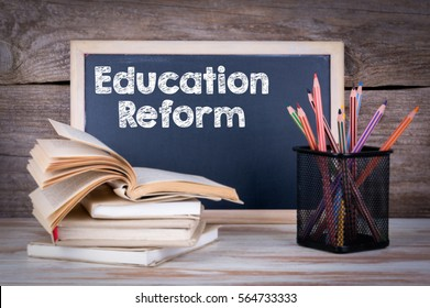 Education Reform. Stack of books, chalk blackboard with pencils on the wooden table.