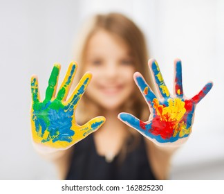 education, school, art and painitng concept - little student girl showing painted hands