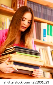 Education school concept. Intelligent female student fashion long hair girl in college library with stack books. Indoor