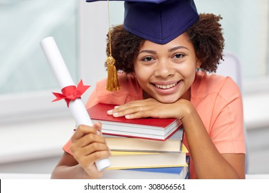 education, school, graduation and people concept - happy smiling african american student girl in bachelor cap with books and diploma sitting at table at home
