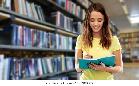 education, school, inspiration and people concept - smiling young woman or teenage student girl in yellow t-shirt writing to notebook by pencil over grey background