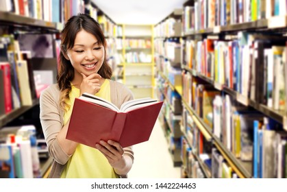 education, school and knowledge concept - happy asian young woman reading book over shelves in librarry background