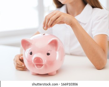 education, school and money saving concept - smiling child putting coin into big piggy bank