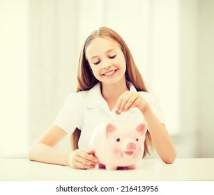education, school and money saving concept - child putting coins into piggy bank