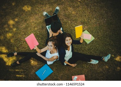 education, school and people concept - Cheerful university students read a book; Asia university.