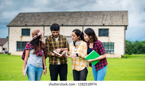 education, school and people concept - Cheerful university students with laptop and read a books on group of students in background at each other at school; Asia studen study.